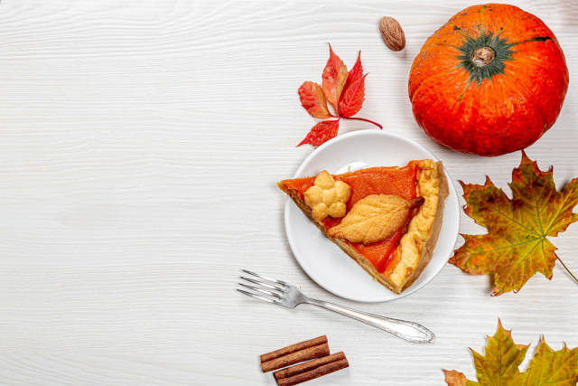 A piece of homemade pumpkin pie with fresh ripe pumpkin, autumn leaves and a fork on the table. The view from the top