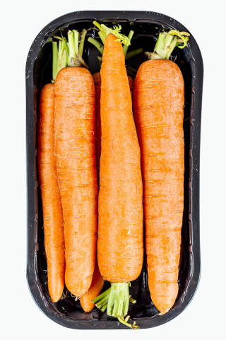 Young carrots in plastic packaging, top view