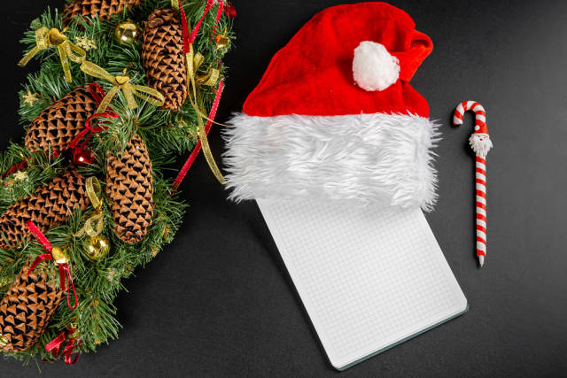 Top view of preparing christmas letter or list on dark background with wreath