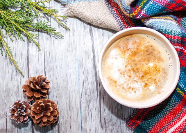 Kaffeetasse, bunter Schal, Kiefernzapfen und Ast