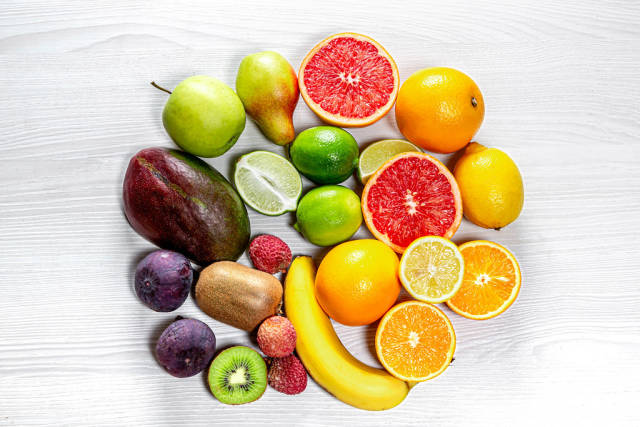 Circle of fresh fruit on white wooden background. Top view