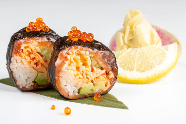 Rolls with nori, salmon, crab, rice, avocado, tobik caviar, salmon caviar and micro-greens