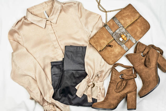 Womens clothing set - skirt, boots, shirt, leather bag on light background