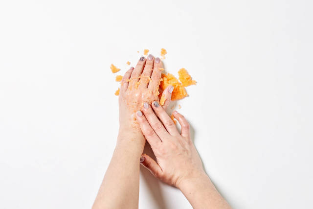 Woman applying on hands citrus fruit natural scrub