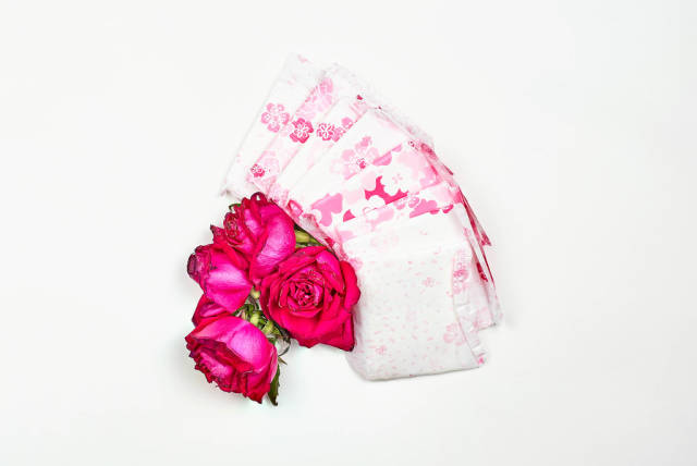 Stack of menstrual pads with red rose on white background