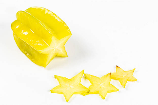 Fresh carambola or star fruit with slices on white background