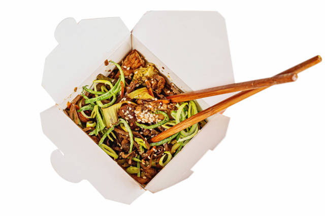 Buckwheat soba noodles with pork, vegetables, spicy sauce in a cardboard box
