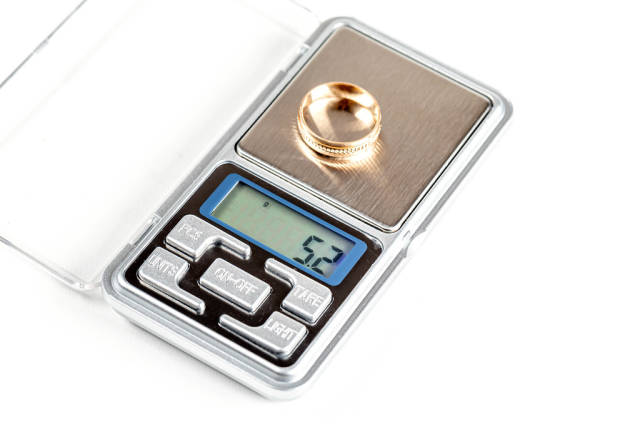 The gold ring is weighed on an electronic jewelry scale