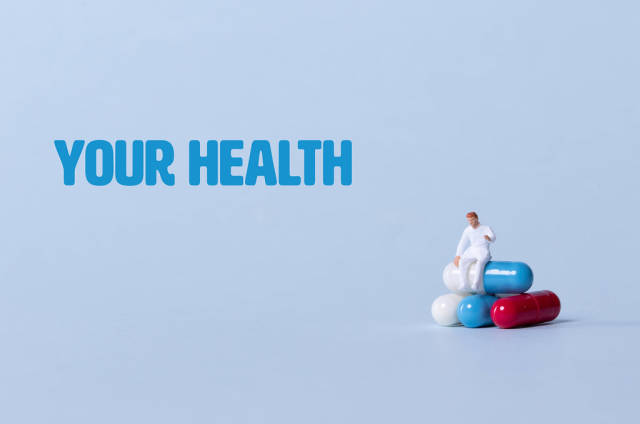 Doctor sitting on a stack of pills with Your Health text