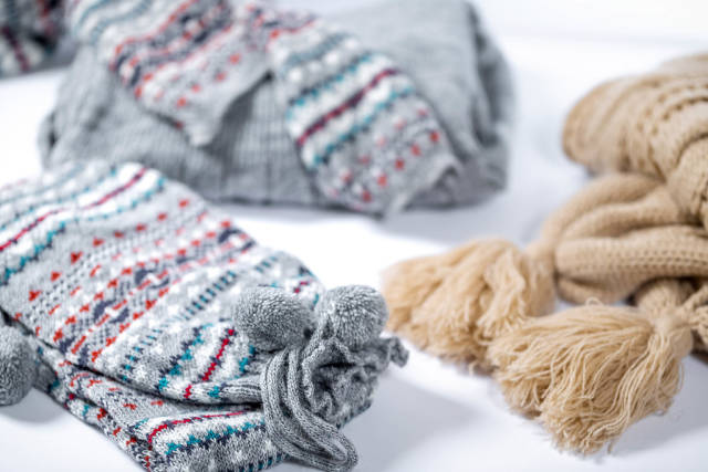 Winter warm clothes on white background