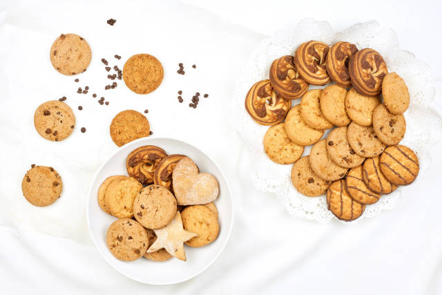 Different sweet cookies on pure white blanket