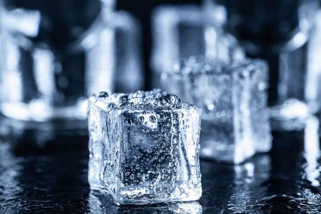 Quadratische Eiswürfel mit Wassertropfen vor Wodka-Gläsern auf dunklem Hintergrund