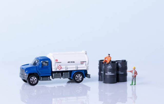 Oil truck and oil barrels with workers