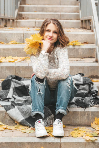 The girl is sitting on the steps and smiling, autumn walk