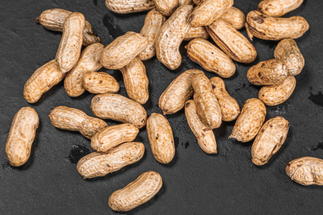 Raw peanuts on black background with peel
