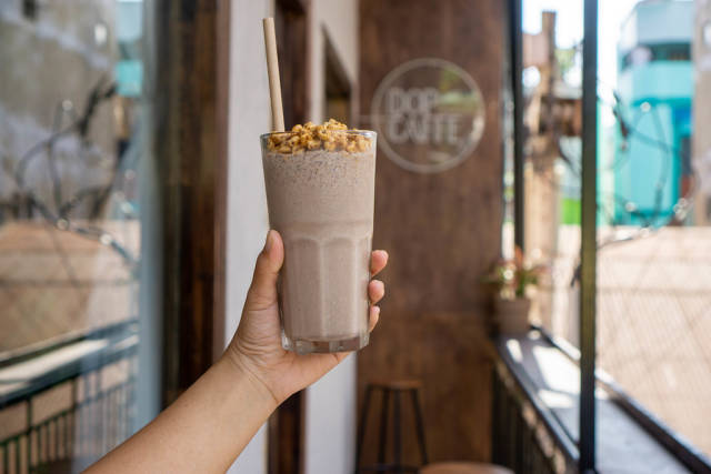 Person holding Cocktail Glass with Cookies and Cream Milkshake, Puffed Rice and Paper Straw on a Balcony of a Cafe