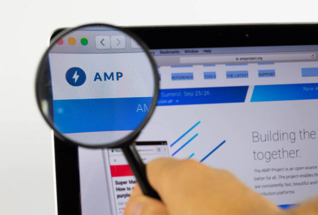 AMP logo on a computer screen with a magnifying glass
