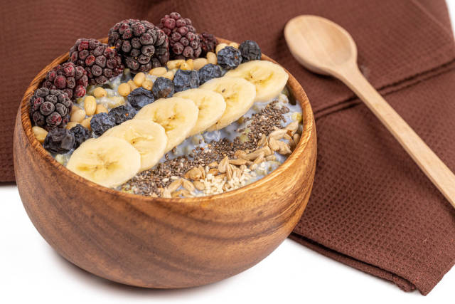 Delicious and healthy breakfast porridge with yogurt, seeds, pine nuts and fruit in a wooden bowl