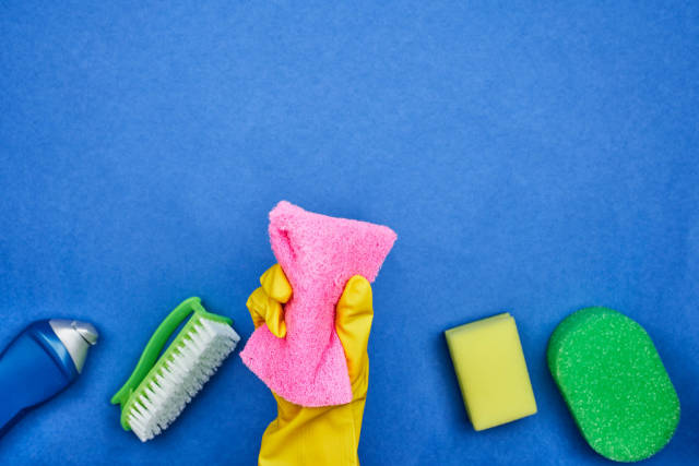 Woman hand with rubber gloves holds a sponge over blue background