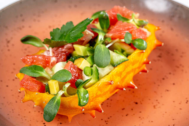 Half a Kiwano stuffed with fresh vegetables, slices of grapefruit and microgreens