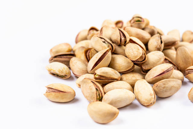 Pistachios above white background