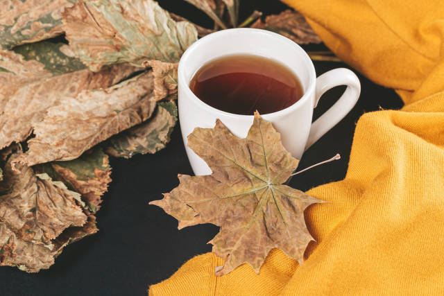 Cup of tea with autumn leaves and yellow scarf