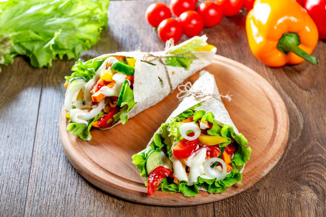 Fresh multi-colored sliced vegetables wrapped in pita bread on the kitchen Board