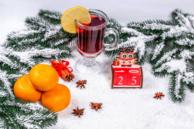 Christmas background with mulled wine and snow-covered Christmas tree branches and tangerines