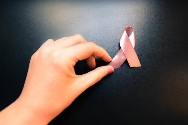 Female hand holding breast cancer awareness ribbon