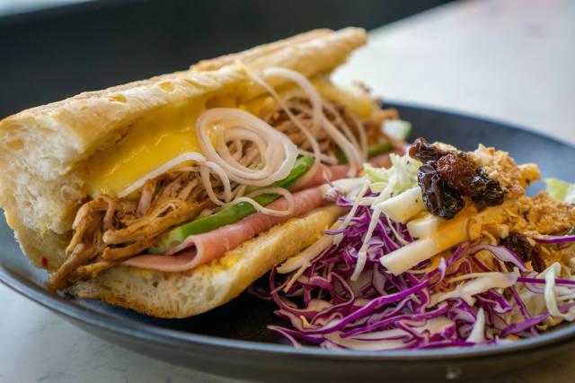 Sandwich mit Pulled Pork, Geschmolzenem Käse, Schinken, Zwiebeln und Gurken neben einem Krautsalat mit Rosinen und Erdnüssen Nahaufnahme