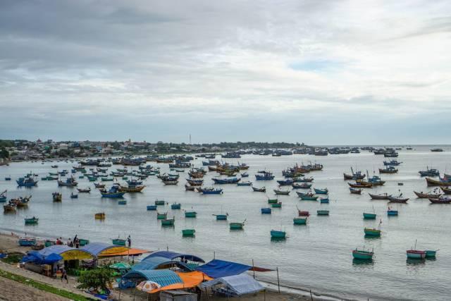 Unzählige traditionell runde Fischerboote und Holzboote im Hafen von Mui Ne, Vietnam