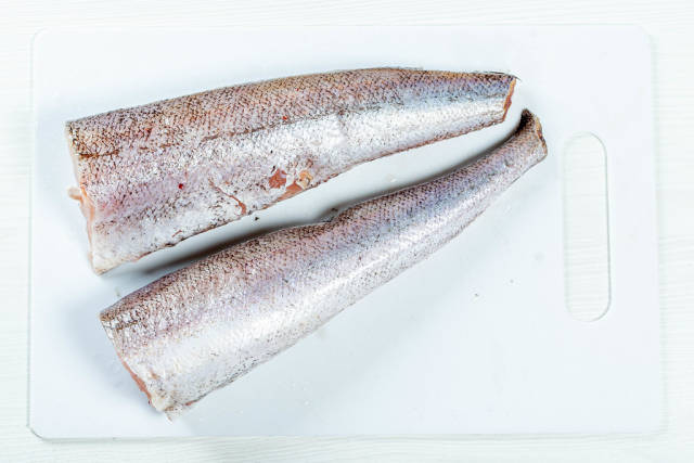 Cleaned raw fish on a white kitchen Board