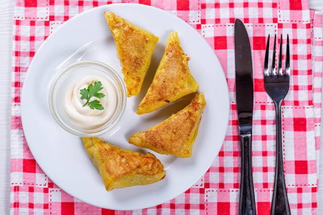 Fried triangles with minced meat inside on a white plate with sauce