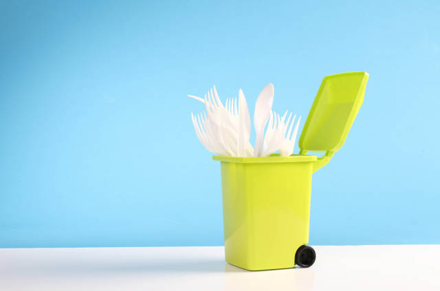 Plastic disposable forks and spoons in a trash can