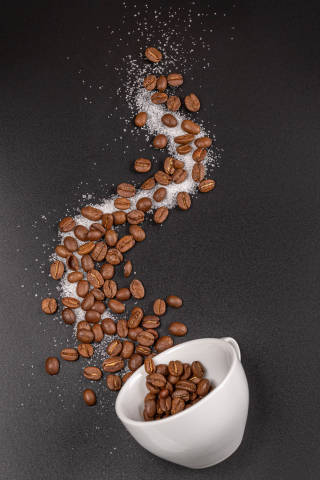 Top view, cup on black background and coffee beans
