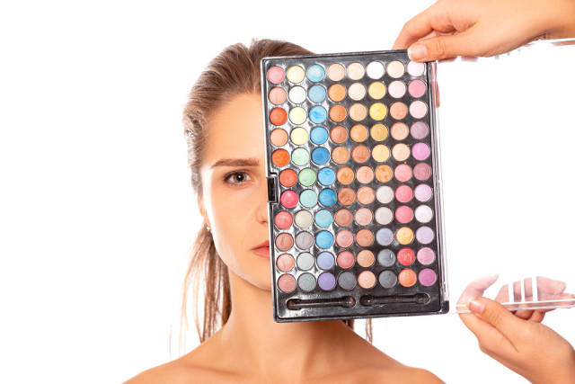 Multicolored set of eyeshadows near the girls face