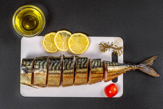 Delicious smoked fish slices on a black background with lemon and tomato, top view