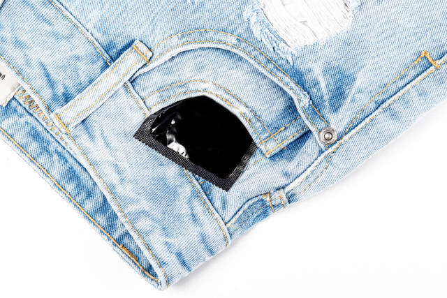 Condom in the pocket of womens shorts. The concept of protection