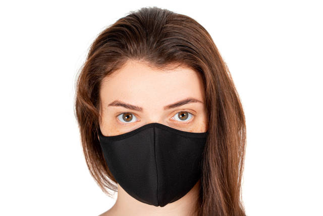 Close-up, portrait of a girl in a black medical mask on white