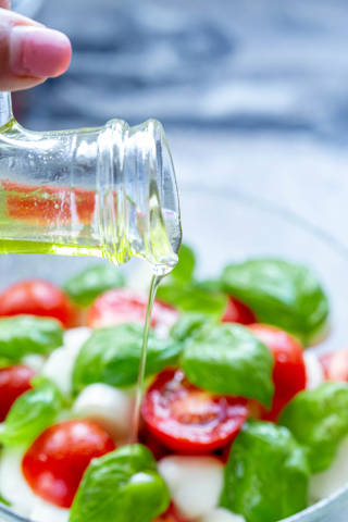 Pouring olive oil into fresh salad