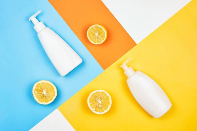 Lemon based shower gel or soap cream bottles on split-colored background