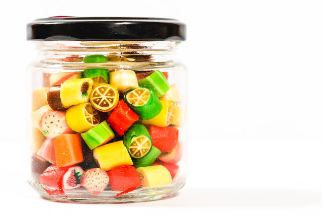 Sweet fruit candies in a glass jar