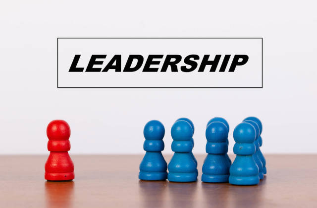 Leadership concept with pawn figurines on table