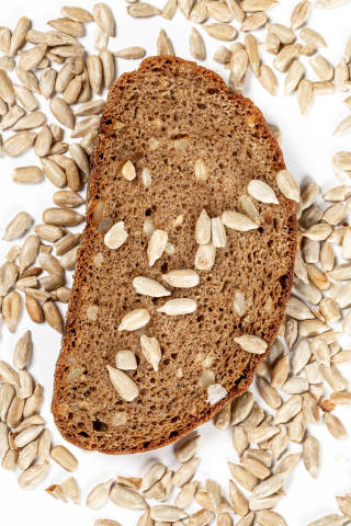 Top view, a piece of rye bread with sunflower seeds on a white background