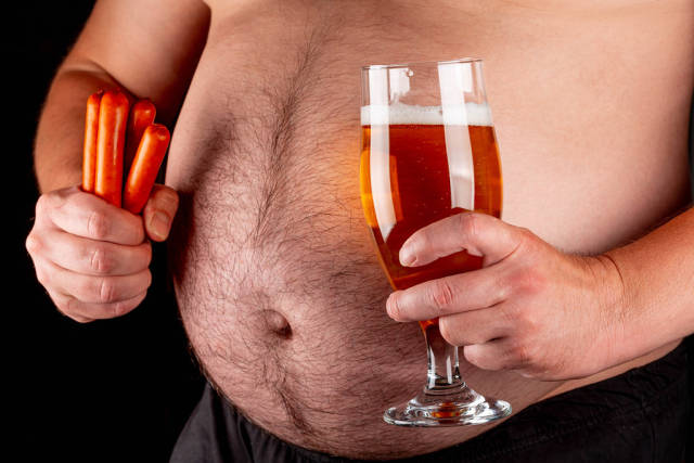 A man holds beer and smoked sausages against a large belly