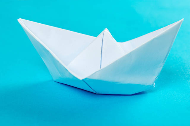 White paper ship on a blue background
