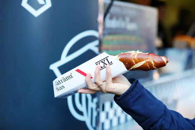 Big German hot dog in womans hand, Sibiu Christmas market