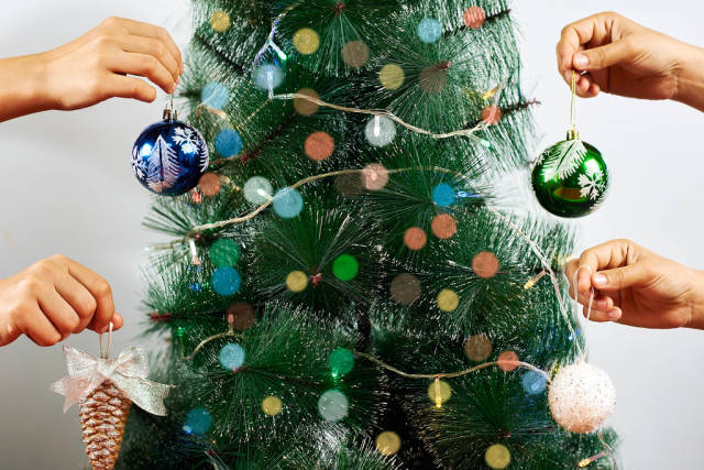 People holding Christmas decorations and baubles around the Xmas tree