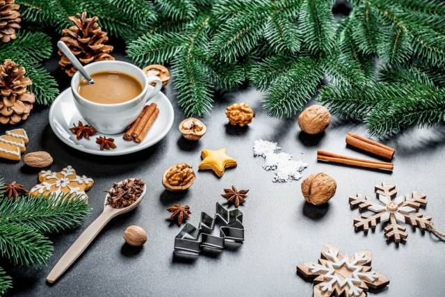 A cup of coffee in Holiday Decoration - Nuts, Cinnamon, Christmas-tree branches, Baking forms