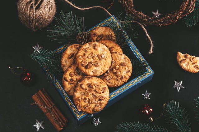 Box of peanut butter cookies in box and Christmas decor on black background
